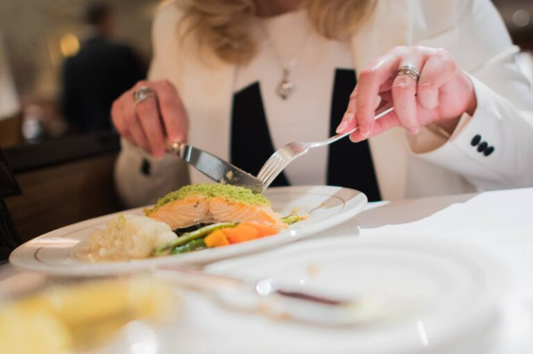 Elegant Restaurant Dinner. Grilled Salmon with Vegetables. Woman Eating Dinner.